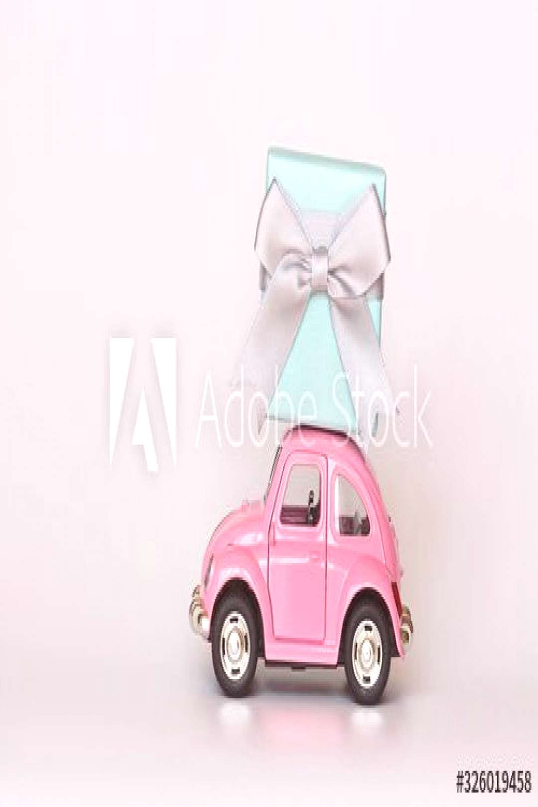 Changxing, China - October 15, 2019 Pink retro toy car delivering gift box on white. ,